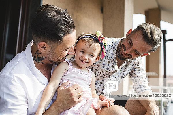 Glückliches schwules Paar mit Tochter zu Hause