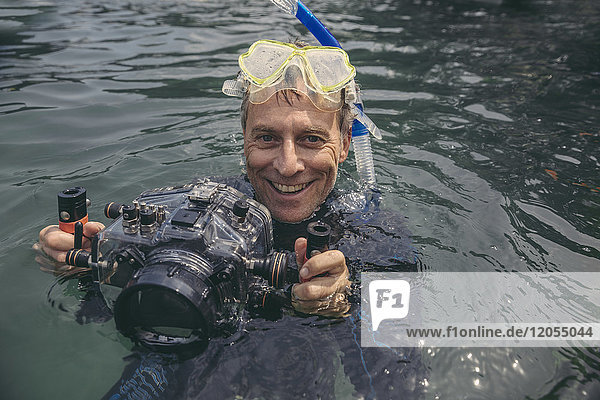 Portrait of happy man with underwater DSLR camera case in a lake