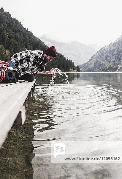 Österreich  Tirol  Alpen  Mann kniend am Steg erfrischend am Bergsee