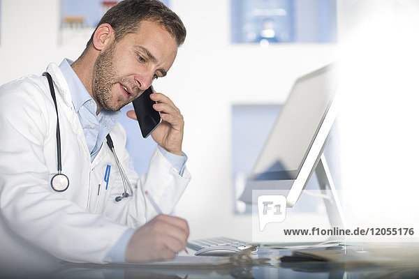 Doctor at desk talking on cell phone