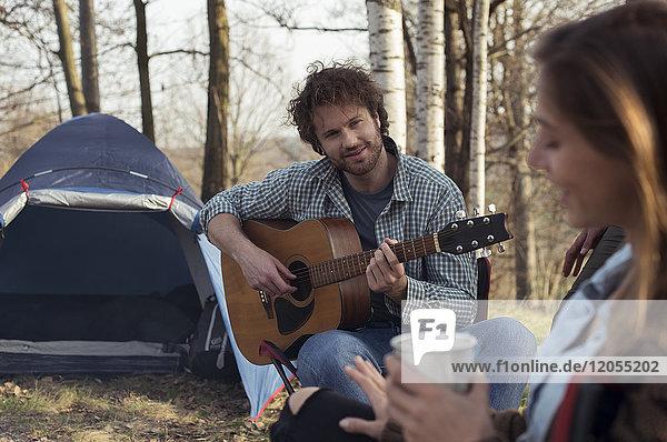 Pärchen-Camping im Wald mit einem Mann  der Gitarre spielt.