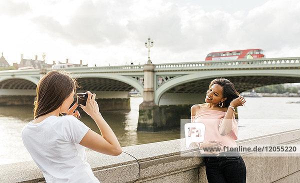 UK  London  Frau beim Fotografieren ihres Freundes in der Nähe der Westminster Bridge