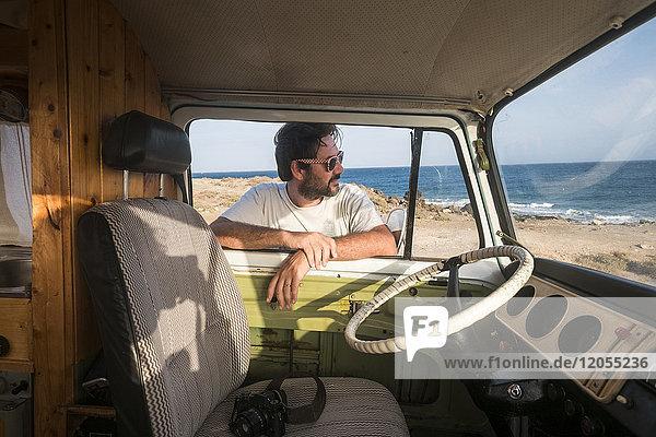 Spanien  Teneriffa  Mann  der sich auf das Autofenster stützt und in die Ferne schaut.