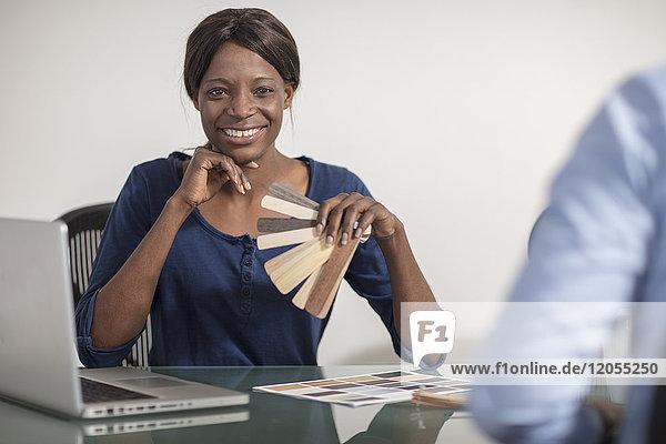 Lächelnde Frau mit Farbmustern im Büro