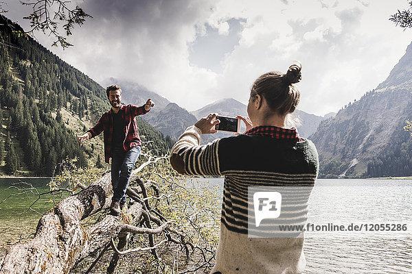 Österreich  Tirol  Alpen  Frau macht Handyfoto von Mann beim Balancieren auf Baumstamm am Bergsee