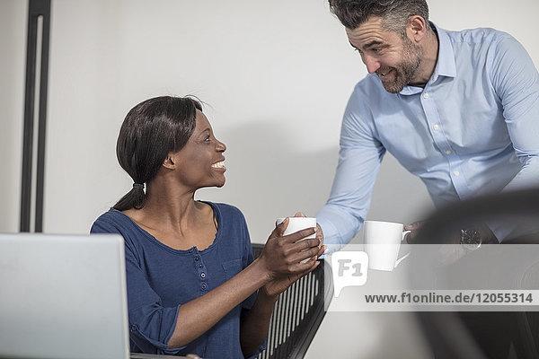 Lächelnde Kollegen mit Kaffeetassen im Büro im Gespräch
