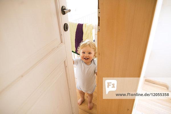 Porträt eines glücklichen Jungen  der die Tür öffnet.