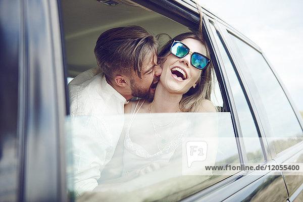 Verspieltes  liebevolles junges Paar im Auto