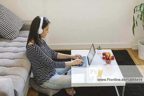 Junge Frau mit Laptop und Kopfhörer zu Hause