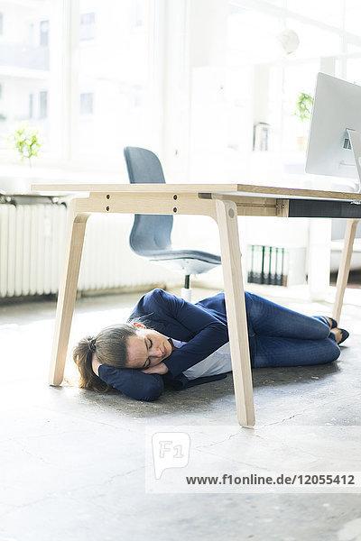 Geschäftsfrau unter dem Tisch liegend im Büro schlafend