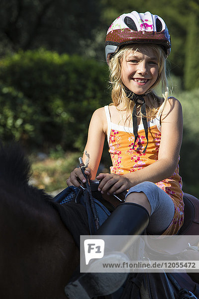 Portrait of happy blond girl riding on horse