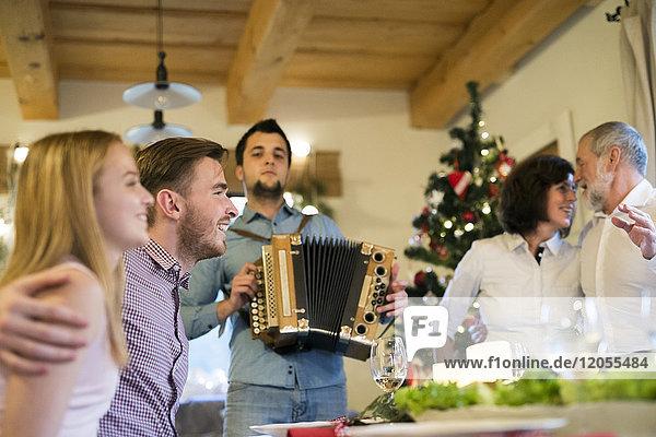 Junger Mann spielt zu Weihnachten Akkordeon für die Familie
