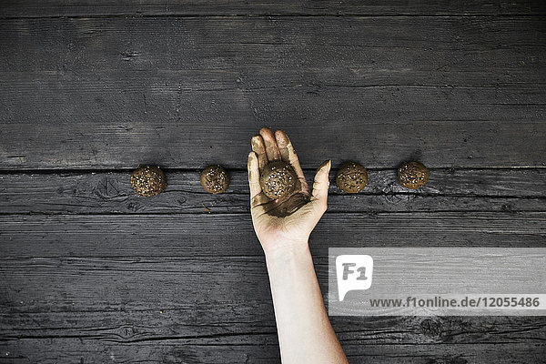 Frauenhand mit Samenbombe
