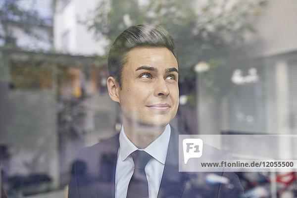 Porträt eines jungen Geschäftsmannes hinter Glasscheibe im Büro mit Blick nach oben