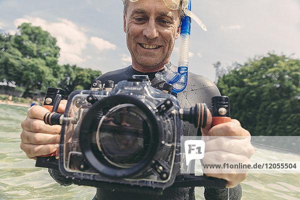 Lächelnder Mann mit Unterwasser-DSLR-Kameragehäuse in einem See