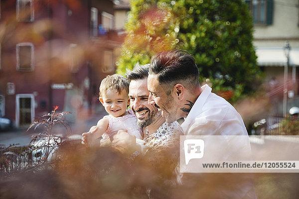 Glückliches schwules Paar mit ihrer Tochter im Freien