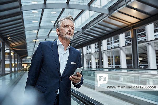 Geschäftsmann mit Smartphone am Flughafen  stehend auf Fahrsteig
