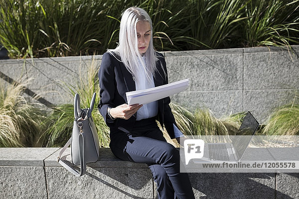 Young businesswoman sitting on a wall in the city with documents and laptop