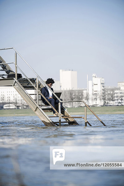 Businessman sitting on stairs at the river using laptop