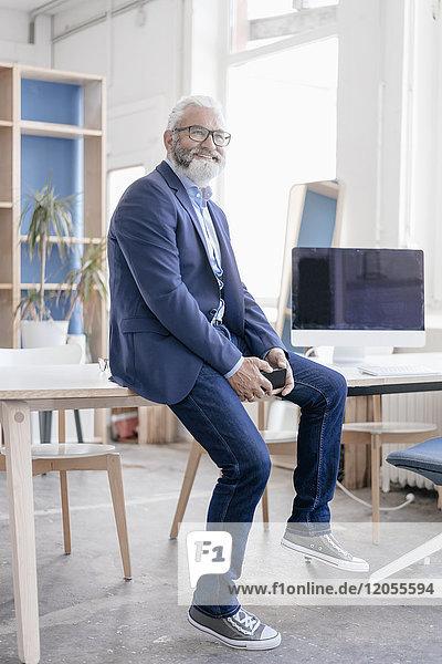 Lächelnder reifer Mann mit Bart und Brille auf dem Schreibtisch sitzend