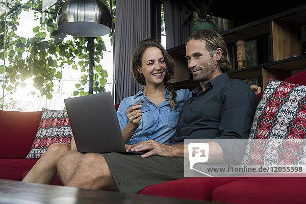 Frau mit Kreditkarte lächelt den Ehemann an  der den Laptop auf einer roten Couch in einem modernen Wohnzimmer anschaut.