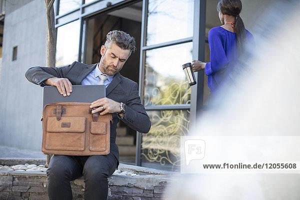 Geschäftsmann steckt seinen Laptop in die Tasche