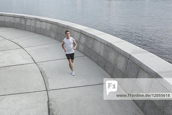Junger Mann läuft am Flussufer entlang