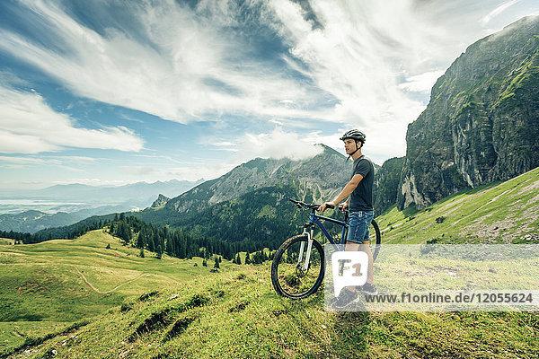 Deutschland  Bayern  Pfronten  junger Mann mit Mountainbike auf der Alm bei Aggenstein