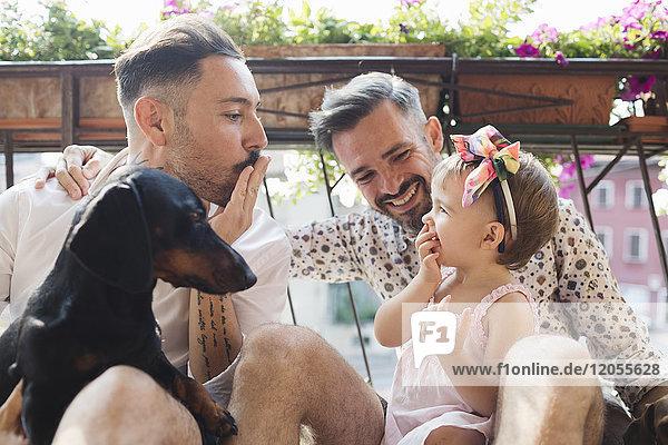 Glückliches schwules Paar mit Tochter und Hund auf dem Balkon