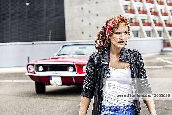 Rothaarige Frau neben Sportwagen auf Parkebene