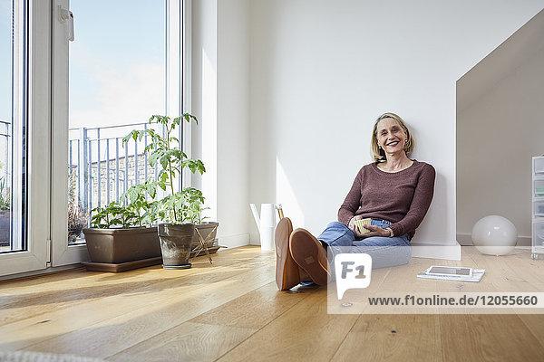 Porträt der lächelnden reifen Frau zu Hause auf dem Boden sitzend