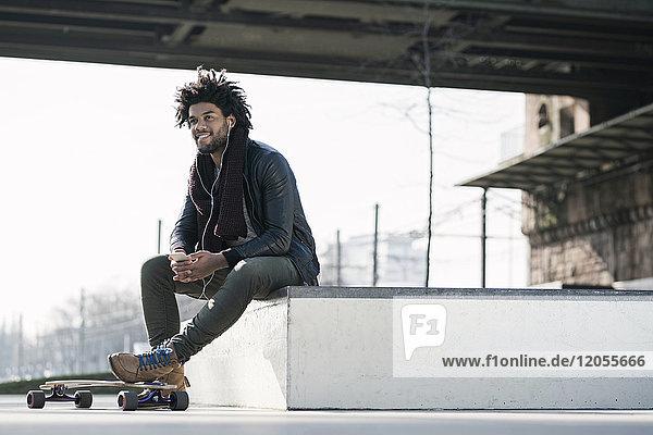 Smiling man with longboard sitting in skatepark under bridge holding a smartphone