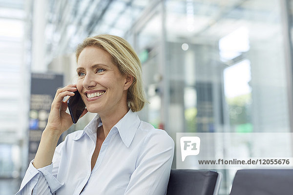 Portrait of laughing businesswoman on the phone waiting at the airport