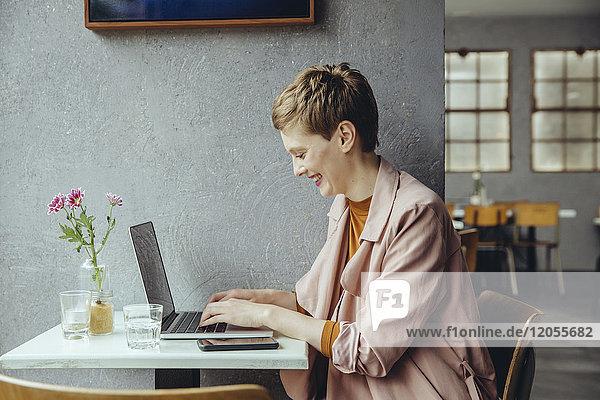 Frau arbeitet im Cafe mit ihrem Laptop