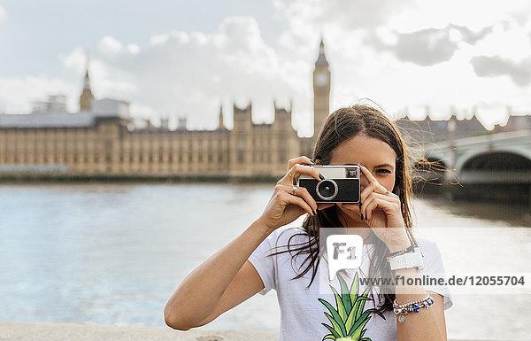 UK  London  beautiful woman taking a picture near Westminster Bridge