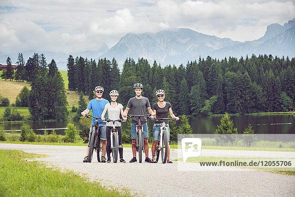 Deutschland  Bayern  Pfronten  Porträt der glücklichen Familie mit Mountainbikes am Ladeside