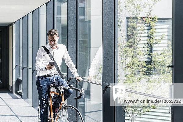 Geschäftsmann mit Handy auf dem Fahrrad im Bürogang