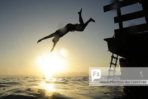 Mann  der bei Sonnenuntergang vom Steg ins Meer springt.