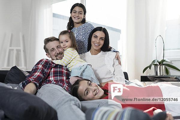 Porträt der Eltern und drei Töchter auf Sofa im Wohnzimmer