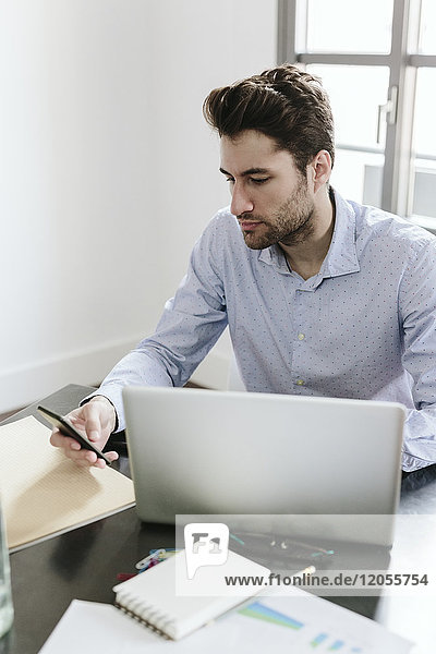 Young businessman working in office  using smartphone and laptop