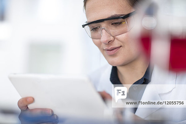 Scientist working in lab looking at tablet