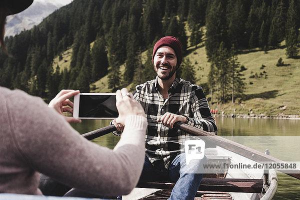 Österreich  Tirol  Alpen  Frau macht Handyfoto von lächelndem Mann im Ruderboot auf dem Bergsee