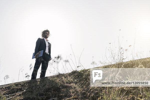 Businessman standing on grassy ridge holding laptop