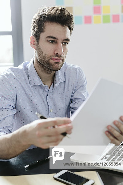 Young businessman working in office  reading documents
