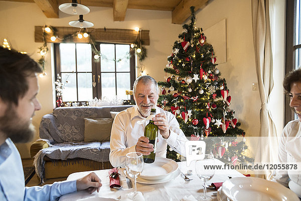Smiling senior man with family holding bottle of wine at Christmas dinner table