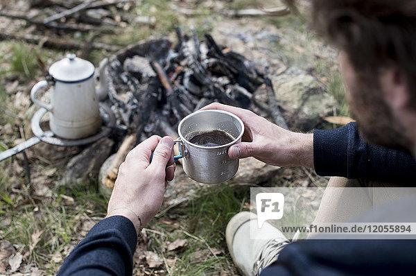 Mann trinkt Kaffee am Lagerfeuer