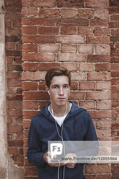 Portrait eines jungen Mannes mit Handy und Kopfhörer an der Ziegelwand