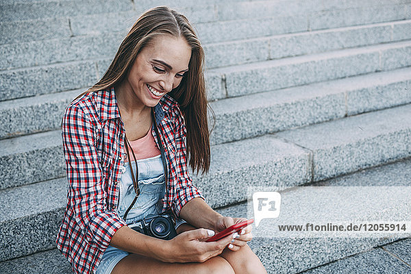 Smiling young woman sitting on stairs looking at cell phone