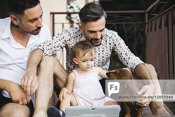 Schwules Paar mit Tochter und Hund auf dem Balkon mit digitalem Tablett Schwules Paar mit Tochter und Hund auf dem Balkon mit digitalem Tablett
