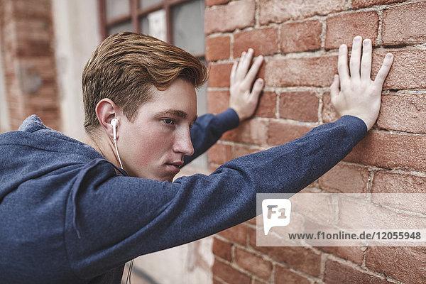 Junger Mann mit Kopfhörern  die sich gegen den Backsteinbau lehnen.